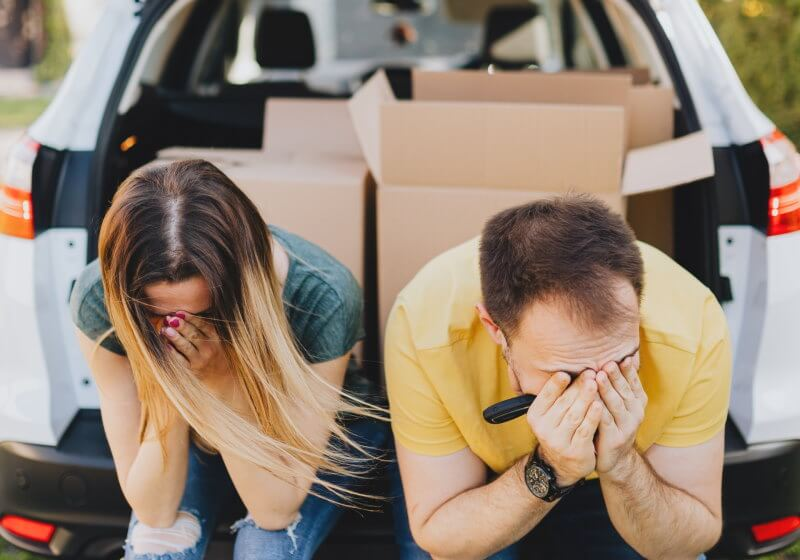 Couple looking upset sitting in their car after their house sale fell through